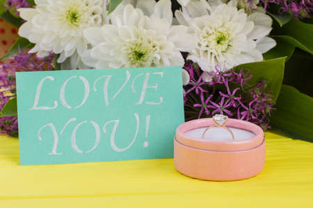 Romantic surprise for Valentine holiday. Gift box with golden ring, fresh flowers and card with inscription Love you on color background. Marry me concept.
