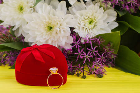 Gold engagement ring and flowers. Golden diamond ring with red velvet box and colorful flowers on yellow background. Romantic surprise for Valentine holiday.