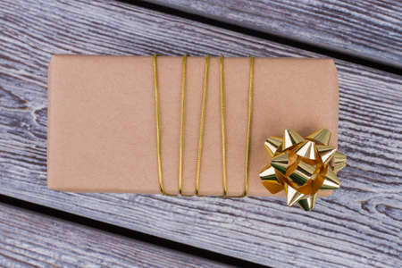 Gift box wrapped in brown vintage paper. Present box packed in kraft paper and tied with golden string, top view. Stock Photo