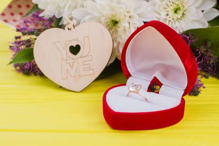 Romantischer Hintergrund mit goldenem Ring und Blumen. Verlobungsring in herzförmiger Box, Blumen und Holzherz auf farbigem Hintergrund. Heirate mich Konzept.