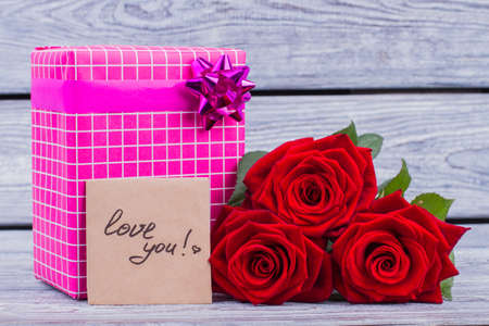 Gift, roses and love you card. Fresh red roses, gift box and love card on wooden background. Saint Valentine Day.