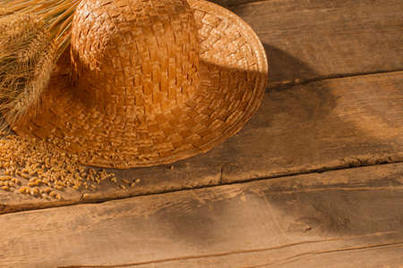 Straw hat and wheat ears on rustic wooden boards. Farmers hat and cereal grain on old wooden floor.