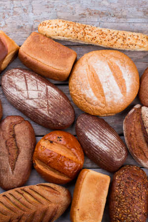 Variety of organic bread on wooden background. Top view of different types of bread. Organic farmers food market.