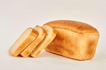 Laib und Scheiben Weißbrot. Frisch gebackenes Brot. Standard-Bild