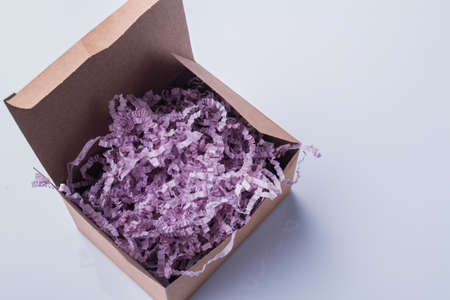 Purple curvy shredded paper in a cardboard box. White isolated background.