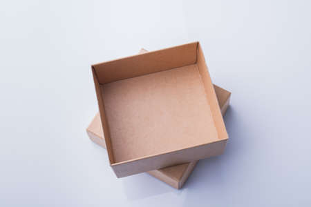 Cardboard box pieces in column, top view. Small empty container parts lyinng one on another, isolated on white.