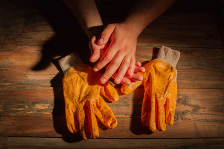 Dirty workers gloves and his hands. Shadow play. Old wood background.