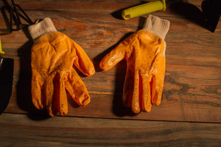 Used dirty garden gloves over wooden table background. Top view, flat lay.