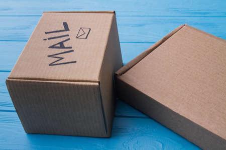 Kartonnen post kartonnen dozen, close-up. Blauwe houten achtergrond. Stockfoto