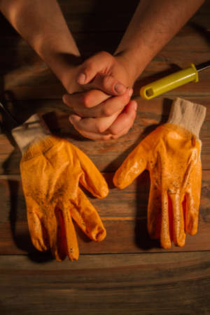 Dirty workers gloves and hands crossed. Close-up orange gloves for gardening.
