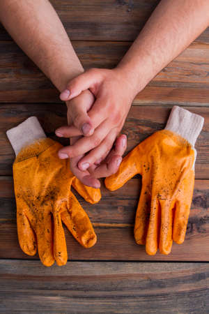 Male hands and workers gloves. Top view. Old brown wooden background.
