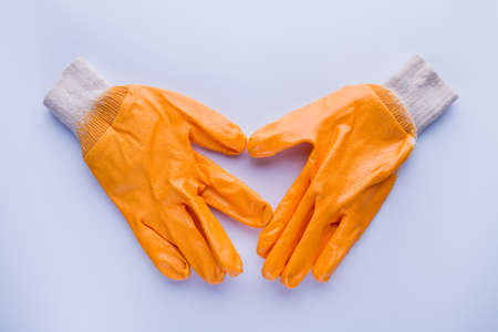 Pair of shiny garden gloves isoalated on white. Orange wet gloves. 写真素材