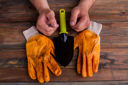 Pair of gloves, trowel and males hands - gardening concept. Close-up, top view, flat lay.
