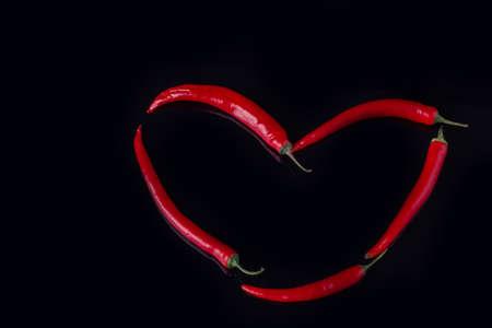 Forma de corazón hecha de pimientos picantes. Corazón hecho con chiles rojos sobre fondo negro. Foto de archivo