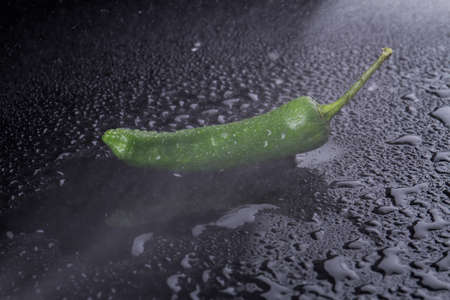 Green chili in focus. Stream of vapor is directed to pepper. Food concept.