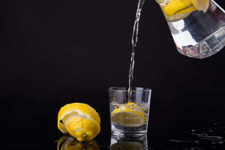 Lemon water is poured to a glass. Refreshing drink in black studio. Food concept. Banque d'images