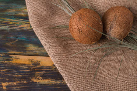 Couple of coconuts on canvas fabric. Exotic nuts in focus. Wooden background.