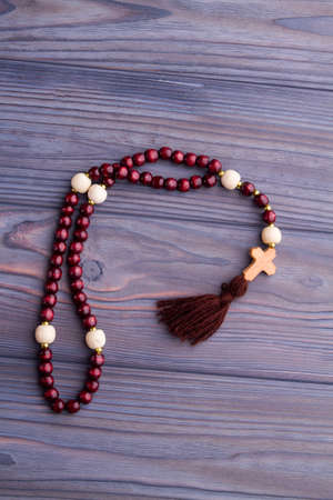 Prayer's rosary with red beads and wooden cross. Faith and believe concept, gray wood background. Imagens