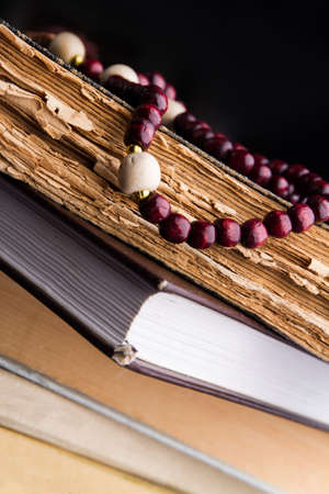 Red wood rosary beads on old holy books. Close-up.