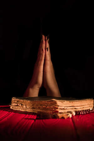 Caucasian praying female hands. Old worn holy bible book on black background. 免版税图像