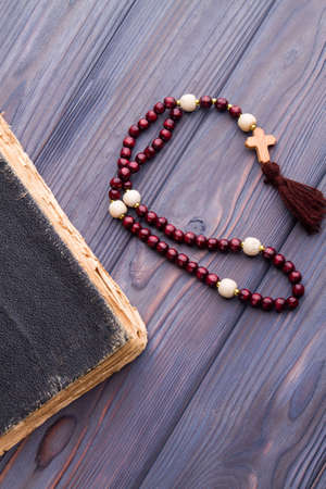 Faith and hope concept. Very old worn holy bible and rosary on wood.