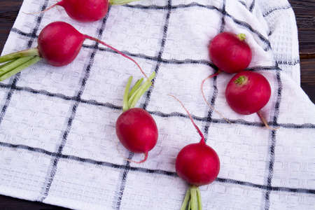 Radish harvest on checkered cloth. Top view.