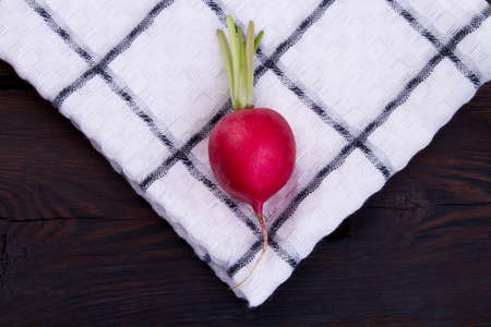 One single ripe radish on checkered towel. Close-up. Cotton cloth.