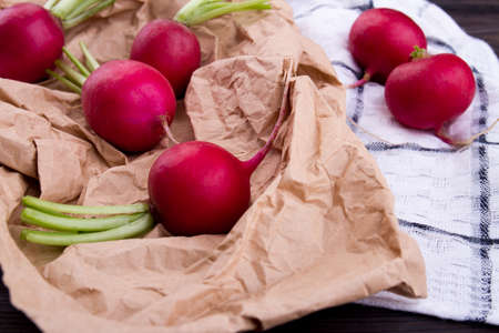 Close-up red ripe radishes. Brown crumpled eco paper.