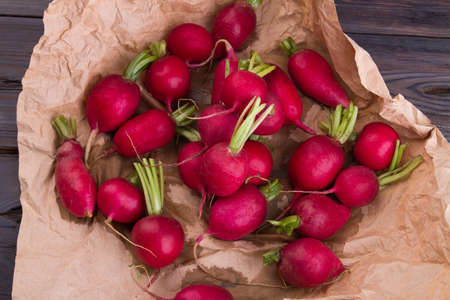 Harvested pile of clean ripe radishes. Heap of vegetables on crumpled brown paper.