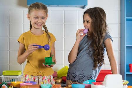 Kleine Mädchen spielen Rollenspiel in der Spielzeugküche. Kinder haben Spaß im Spielzimmer. Standard-Bild