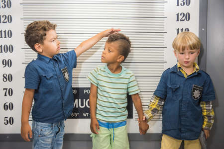 Elementary school boys playing police and prisoner. Children at indoor game center.
