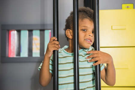 Little boy playing prisoner indoor. Role play at the game center for children.