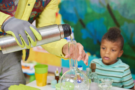 Science show for children. Scientist pouring liquid in glass flask. Kids entertainment and education.