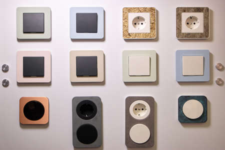 Various switchers and sockets texture. White wall with rosettes. 版權商用圖片