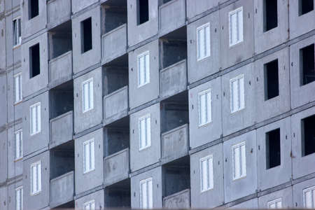 Facade of unfinished high-rise concrete building. Grey skyscraper close up.