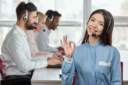 Asian female operator shows ok gesture. Smiling cheerful japaneese girl working in call center operator and showing ok gesture against colleagues background. 版權商用圖片