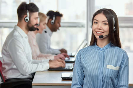 Portrait of smiling japaneese girl with headset in call center office. Asian woman in striped shirt sitting in front of colleagues working typing in bright office. 版權商用圖片