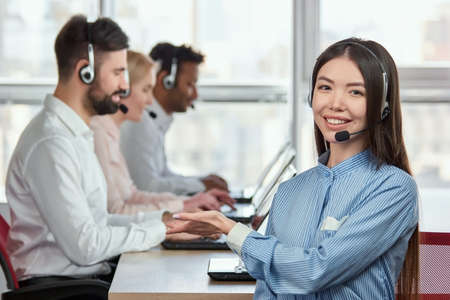 Young female operator pointing hand at co-workers. Smiling cheerful asian japaneese girl working in call center and pointing at colleagues. They are my co-workers. Stock Photo