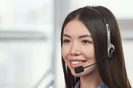 Female smiling opearator. Half-turned young cheerful smiling support phone female operator in headset at office.