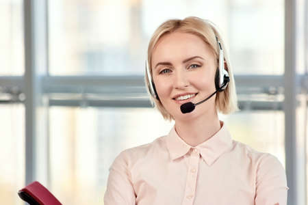 Mature blond woman wearing a telephone headset. Blond lady in white shirt in headphones with microphone in bright office.