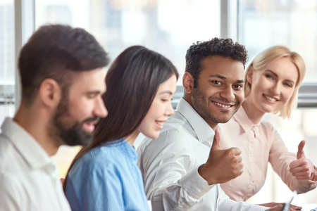 Young black man and mature woman show thumb up. Happy office workers shows thumbs up, distant focus.