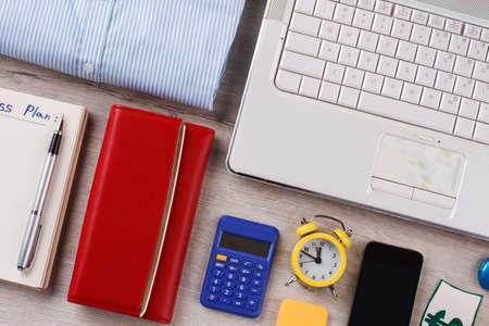 Wallet, pocket calculator and clock. Flatlay of busy office woman.