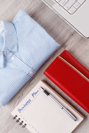 Shirt, laptop and wallet. Typical flatlay of businesswoman.