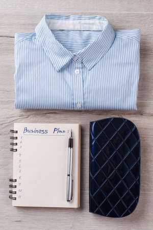 Womens flatlay. Shirt, planner with digits and pen, case. Office concept. 版權商用圖片