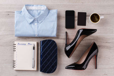 Shirt, notebook with pen. Office womans flatlay on wooden table. Look in dark shades.