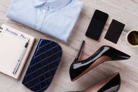 Office womens flatlay on table close up. Shirt, case and heels. Look in dark shades. 版權商用圖片