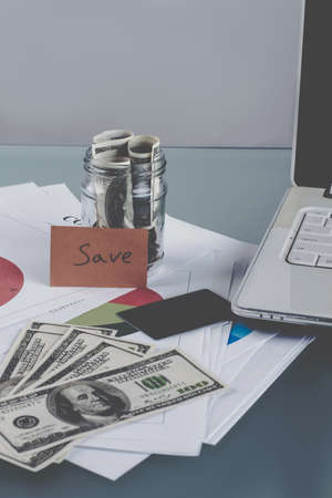American dollars and office stuff close up. Better save money, not waste. Economic concept. Banco de Imagens