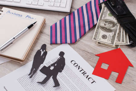 Money, paper house and contract in focus. Joint property. Affairs between spouses.