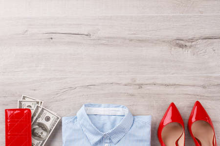 Office womans flatlay on wooden table. Office shirt, heels and wallet with american dollars. Office concept. 版權商用圖片