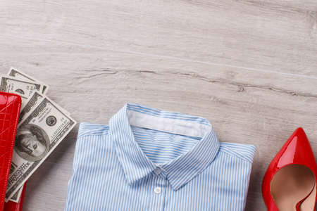 Office shirt, heels and wallet with money. Office womans flatlay on wooden table. Office concept.